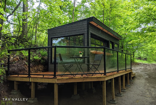 A wooden hut with lots of glass on a wooden platform in the middle of a forest